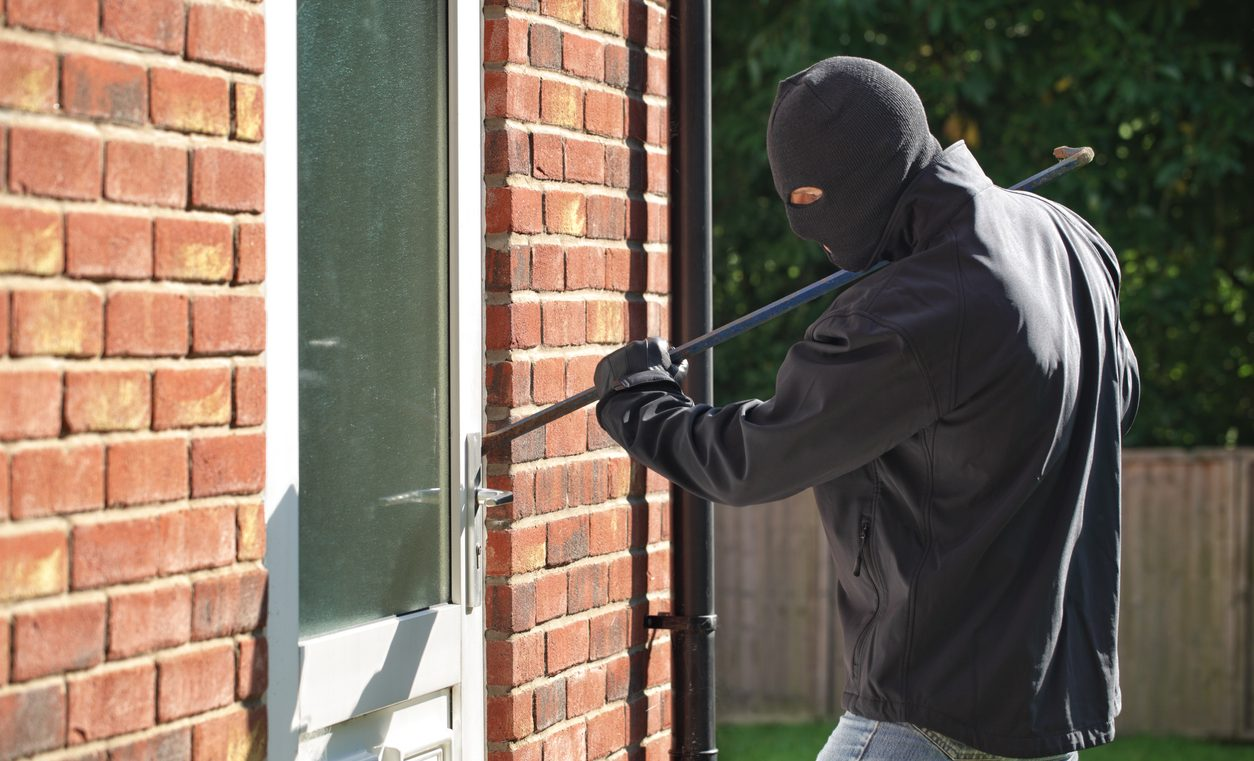 A man breaking into a house: a reason why residential security is important