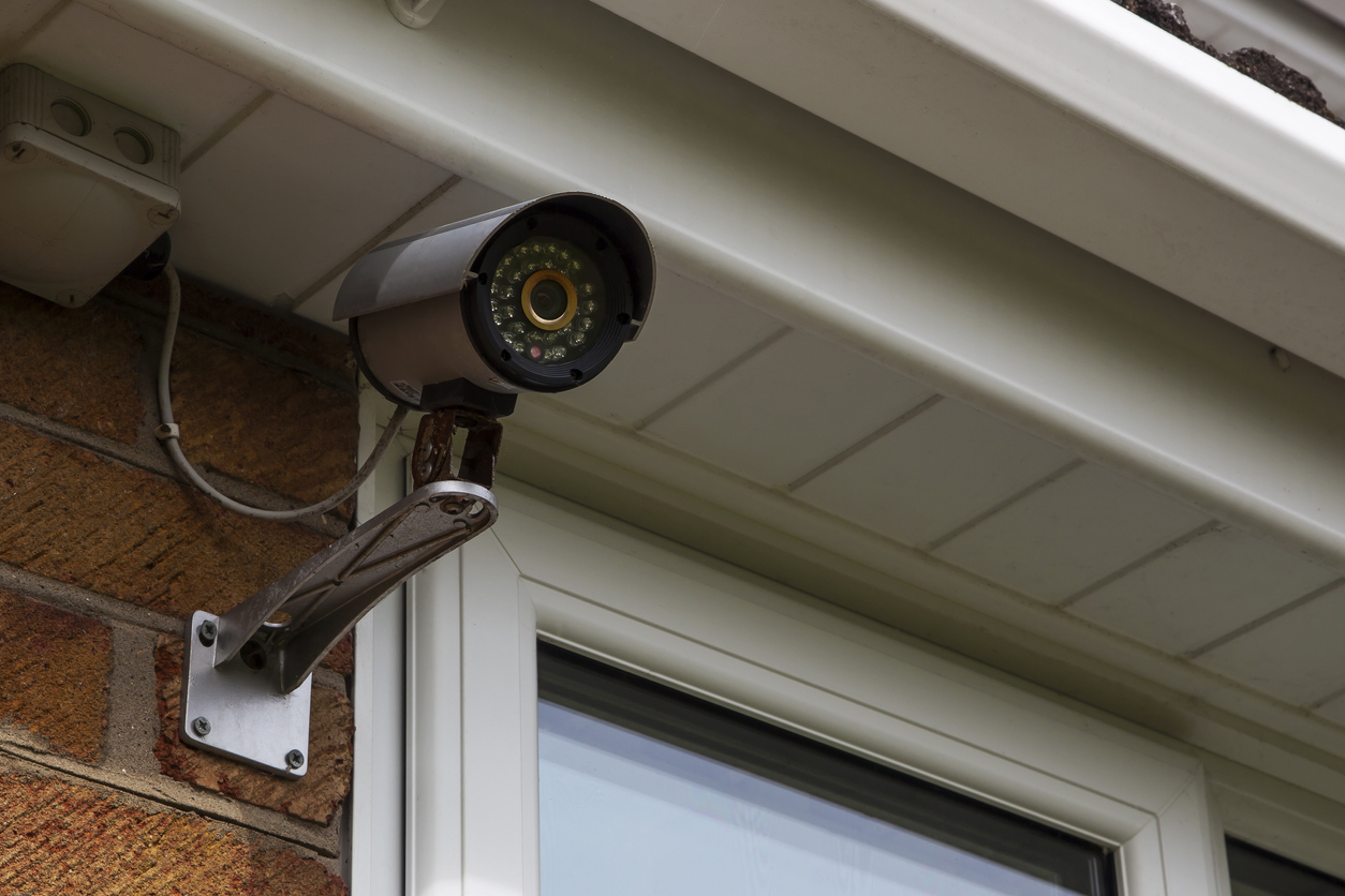 A home security camera system mounted on the exterior wall