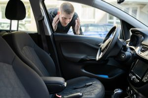 man locked out of his car, keys on drivers seat